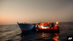 Migrants sailing in a crowded wooden boat carrying more than seven hundred migrants, are helped by members of an NGO during a rescue operation at the Mediterranean sea, about 13 miles north of Sabratha, Libya, Aug. 29, 2016.