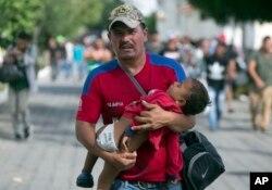Một người di dân ẵm con nhỏ trong khi ông đi bộ về hướng Hoa Kỳ. Ảnh chụp tại Chiquimula, Guatemala, hôm 16/10/2018.