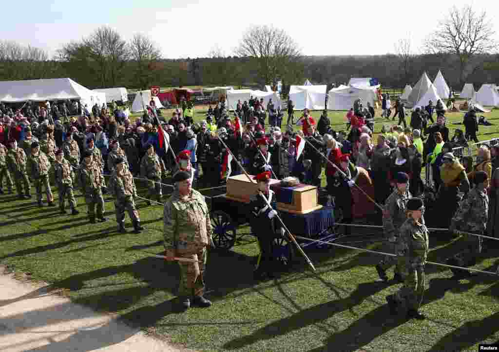 Cadets wheel Richard III's coffin on to the battefield at Bosworth, near Leicester, central England. Richard III's remains are being carried in procession through Leicestershire on its way to the cathedral where they will be reburied. The body of Richard III, who died at the battle of Bosworth in 1485, was found under a car park in 2012.