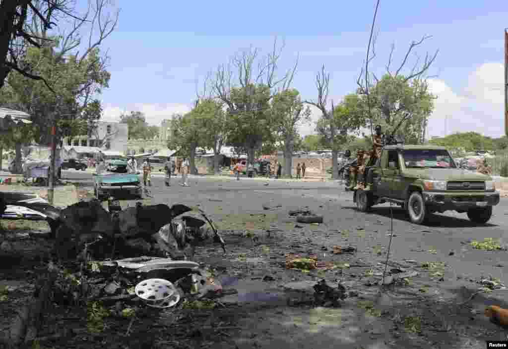 O exército somali passa pelo local onde carro-bomba explodiu junto a um café em Mogadíscio, Somália, Fev. 27, 2014.