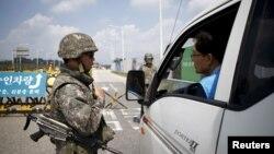Binh sĩ Hàn Quốc kiểm tra xe cộ tại 1 trạm kiểm soát trên cầu Đại Thống nhất dẫn tới làng Bàn Môn Điếm, phía nam khu phi quân sự (DMZ) ngăn cách hai miền Triều Tiên, ở Paju, Hàn Quốc, 22/8/2015.
