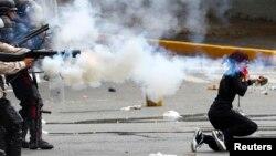 Una manifestante es atacada por la espalda por policías nacionales durante los enfrentamientos en El Cafetal, al este de Caracas.