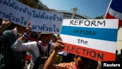 FILE - Anti-government protesters carry placards during a mass rally outside the house of Prime Minister Yingluck Shinawatra in Bangkok, Dec. 22, 2013.