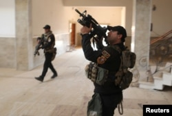 Iraqi special forces search a building located inside a church compound in Bartella, east of Mosul, Iraq on Oct. 21, 2016.