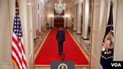 El presidente Obama camina por el corredor de entrada de regreso al salón Azul tras el histórico anuncio de la muerte de Osama bin Laden