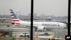 FILE - In a March 13, 2019 file photo, an American Airlines Boeing 737 MAX 8 sits at a boarding gate at LaGuardia Airport in New York. American Airlines said on April 7, 2019 it is extending by over a month its cancellations of about 90 daily flights