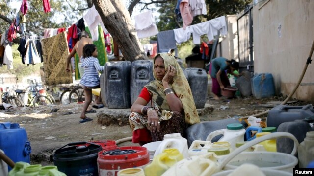 A woman waits to fill her containers with water from a municipal tap in New Delhi, India, Feb. 21, 2016. Protests by the Jat community have disrupted water supplies to about 10 million people.