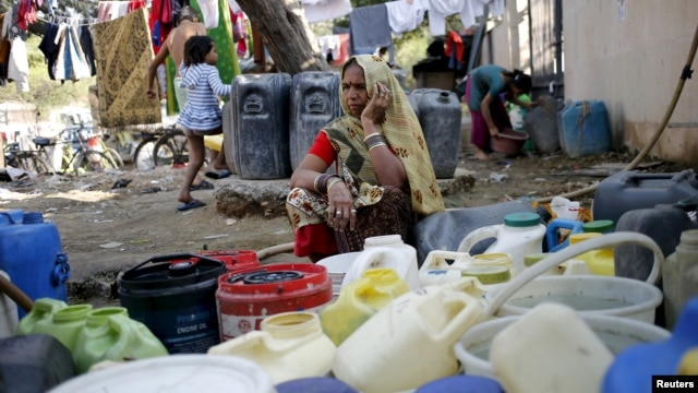 A woman waits to fill water in her containers from a municipal tap in New Delhi, India, Feb. 21, 2016.  India deployed thousands of troops in a northern state to quell protests that have severely hit water supplies to Delhi.