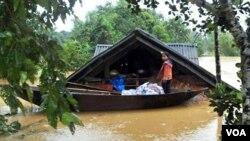 Seorang anak perempuan Vietnam berdiri di atas perahu di depan rumahnya yang terendam air minggu lalu. Banjir parah menewaskan paling sedikit 30 orang di Vietnam tengah.