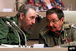 In this file picture taken on December 20, 1999 Cuban President Fidel Castro (L) confers with his brother Raul Castro