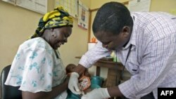 Bà Salama (trái) ở Kenya cho con bà tham gia chương trình thử nghiệm lâm sàng vắcxin ngừa sốt rét