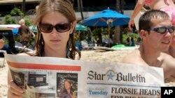 Turistas leen las últimas noticias sobre la llegada de la tormenta tropical Flossie a Hawai.