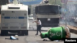 A protester throws stones at police vehicles in the Kurdish dominated southeastern city of Diyarbakir, Turkey, September 13, 2015.