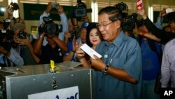 Cambodia's Prime Minister Hun Sen, center, casts his ballot at a polling station in Takhmau town, south of Phnom Penh, Cambodia, Sunday, July 28, 2013.