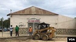 Carlos Cardoso (camisa verde) e a sua maquinária que ajuda Benguela