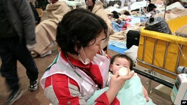 Japanese Red Cross Society worker feeds baby at relief center
