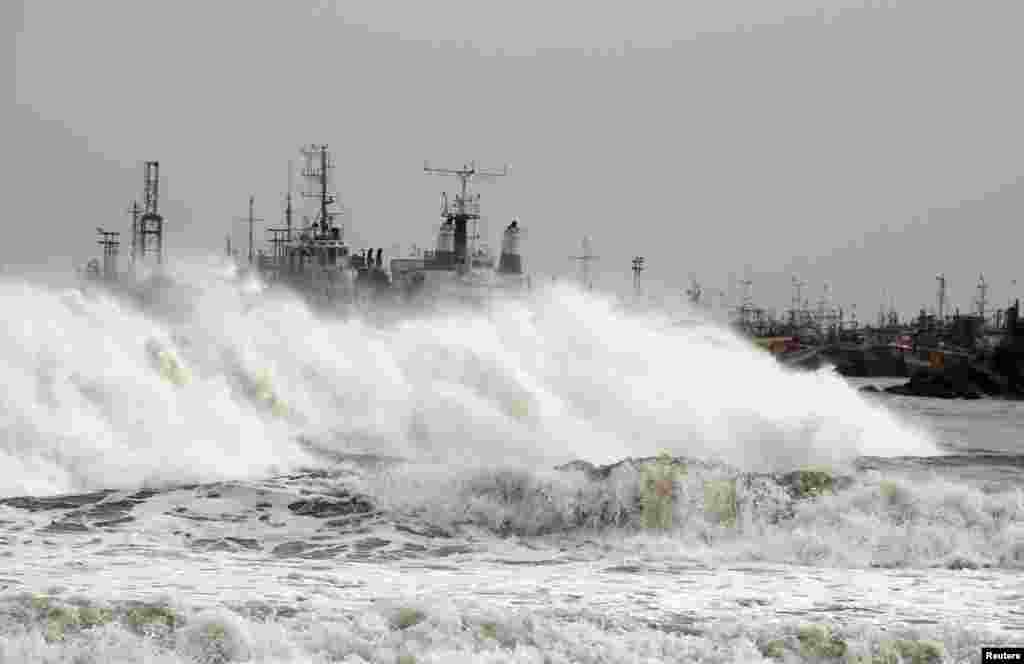 A big wave smashes into a breakwater at a fishing harbor in Jalaripeta, Andhra Pradesh, India, Oct. 11, 2013.