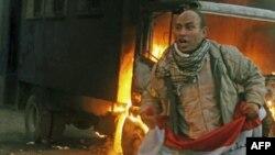 Một người biểu tình phản đối cầm lá cờ Ai Cập bên cạnh chiếc xe cảnh sát bị đốt cháy trong vụ xô xát giữa người biểu tình và lực lượng an ninh ở Quảng trường Tahrir, hôm 19/11/11
