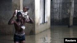 Un habitant de Lagos porte un enfant dans le quartier d'Ikorodu, inondé en août 2007