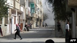 People run for cover from smoke after a shelling in the Karm al-Zeitoun area in Homs, Syria, March 12, 2012. (Reuters)