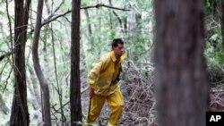 Lucas Handy de la brigada de bomberos voluntarios corta arbustos y maleza cerca a la zona del incendio.