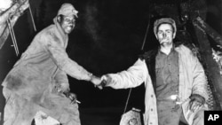 """This Oct. 25, 1942, photo provided by the U.S. Army Corps of Engineers Office of History, shows Corporal Refines Slims, Jr., left, and Private Alfred Jalufka shaking hands at the """"Meeting of Bulldozers"""" for the ALCAN Highway in the Yukon Territory in Beaver Creek, Alaska. Nearly 4,000 segregated black soldiers helped build the highway across Alaska and Canada during World War II, a contribution largely ignored for decades but drawing attention as the 75th anniversary approaches."""