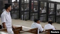 "FILE - Islamist defendants stand behind bars in the case known as the ""Kerdasa massacre'' in Cairo, Eygpt, June 23, 2014."