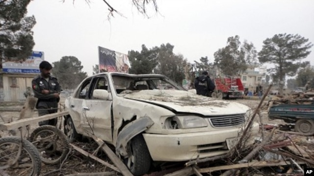 Afghan policemen inspect a car hit by a suicide car bomb attack in Khost province, February 18, 2011