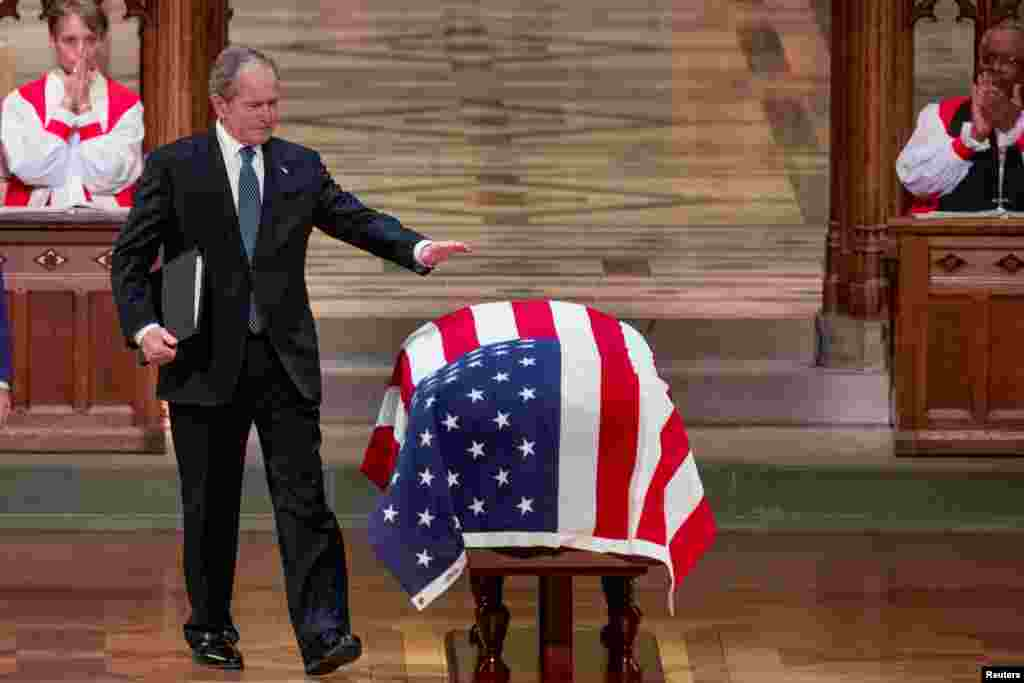 An emotional former President George W. Bush, the 43rd president of the U.S., touches the flag-draped casket of his father, the nation's 41st president, George H.W. Bush, after speaking during his state funeral at the National Cathedral, in Washington.