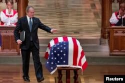 Bivši predsednik SAD Džordž Buš mlađi dodiruje kovčeg sa posmrtnim ostacima svog oca