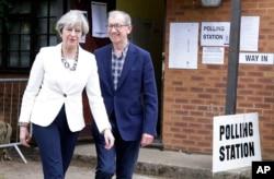 La primera ministra británica Theresa May y su esposo Philip salen de votar en su distrito de Maidenhead, Inglaterra.