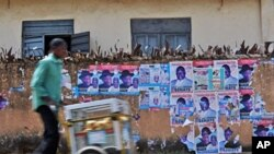 A Nigerian man hawks snacks along a street lined with destroyed posters advertising Presidential candidate Jonathan Goodluck at Jos, Apr 15 2011