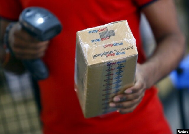 FILE - A worker of Indian e-commerce company Snapdeal.com scans barcode on a box after it was packed at the company's warehouse in New Delhi.