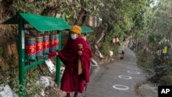 Seorang biksu Buddha Tibet di pengasingan memutar roda doa di jalan yang ditandai dengan lingkaran bagi para pemilih yang antre untuk memberikan suara, guna memastikan jarak sosial, selama pemilu di Dharamsala, India, Minggu (3/1).