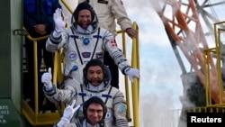 Dari atas ke bawah: Andreas Mogensen, Aidyn Aimbetov dan Sergei Volkov melambaikan tangan saat menaiki pesawat Soyuz TMA-18M di Baikonur Cosmodrome, Kazakhstan (2/9). (Reuters/Kirill Kudryavtsev)
