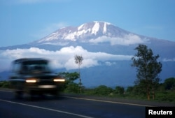 FILE - A vehicle drives past Mount Kilimanjaro in Hie district, Tanzania, Dec. 10, 2009.