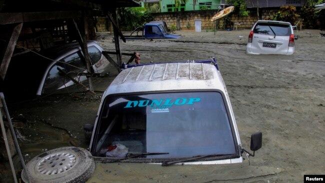 Mobil-mobil tenggelam akibat bencana banjir dan tanah longsor di Sentani, Papua hari Minggu (17/3). (Foto. Antara/Gusti Tanati)