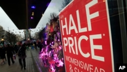 Christmas shoppers walk past a sale sign in the window of a shop in Oxford Street in London, Friday, Dec. 18, 2015.