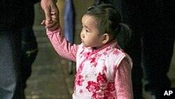 台湾生育率已经降到每名妇女生产不到一名婴孩的水平。图为一个男孩牵着妹妹和家人在庙里拜佛资料照。