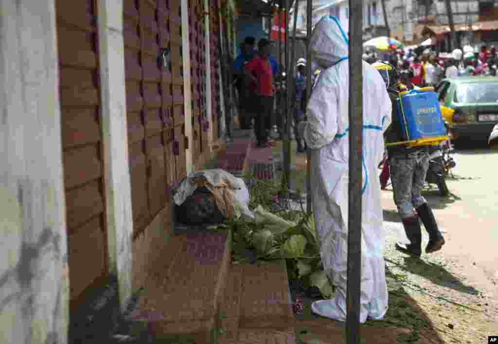 Heath workers collect samples from the body of a person suspected to have died from the Ebola virus, as it lies on the street covered in leaves in Freetown, Sierra Leone.