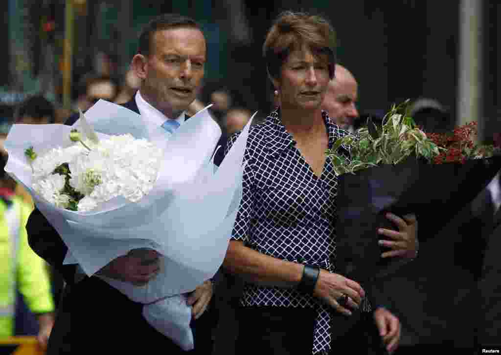 Australian Prime Minister Tony Abbott and his wife Margie prepare to place floral tributes near the cafe in central Sydney, December 16, 2014.
