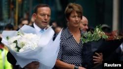 PM Australia Tony Abbott dan istrinya Margie bersiap meletakkan karangan bunga untuk menghormati para korban penyanderaan di sebuah kafe di pusat kota Sydney (16/12).