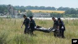 Члены поисковой группы выносят останки одного из погибших в крушении малазийского авиалайнера, упавшего на юго-востоке Украины