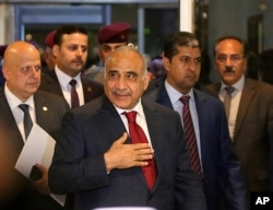 FILE - Prime Minister-designate Adel Abdul-Mahdi, center, arrives to the parliament building, in the heavily guarded Green Zone, in Baghdad, Iraq, Oct. 24, 2018.
