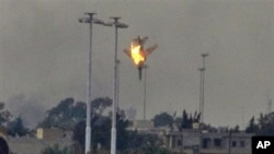 A warplane is seen being shot down over the outskirts of Benghazi, eastern Libya, March 19, 2011