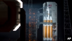 This NASA image shows the agency's Orion spacecraft mounted on a United Launch Alliance Delta IV Heavy rocket, with a mobile service tower rolling back, Dec. 4, 2014.