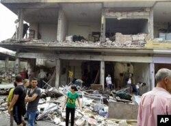 ຮູບພາບທີ່ພິມເຜີຍແຜ່ ໂດຍອົງການຂ່າວ SANA ຂອງທາງການຊີເຣຍ ທີ່ສະແດງໃຫ້ເຫັນ ປະຊາຊົນ ໄປໂຮມຊຸມນຸມກັນ ຢູ່ບ່ອນເກີດລະເບີດ ທີ່ບ້ານ Mukharam al-Fawkan ທາງກ້ຳຕາເວັນອອກ ຂອງເມືອງ Homs. (ວັນທີ 5 ພຶດສະພາ 2016)