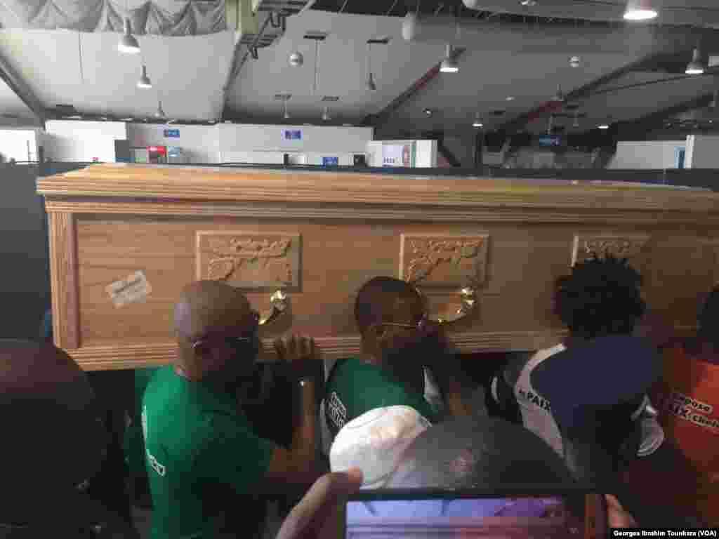 Le corps de Tioté est porté par ses camarades de la sélection à l'aéroport d'Abidjan, le 15 juin 2017. (VOA/Georges Ibrahim Tounkara)