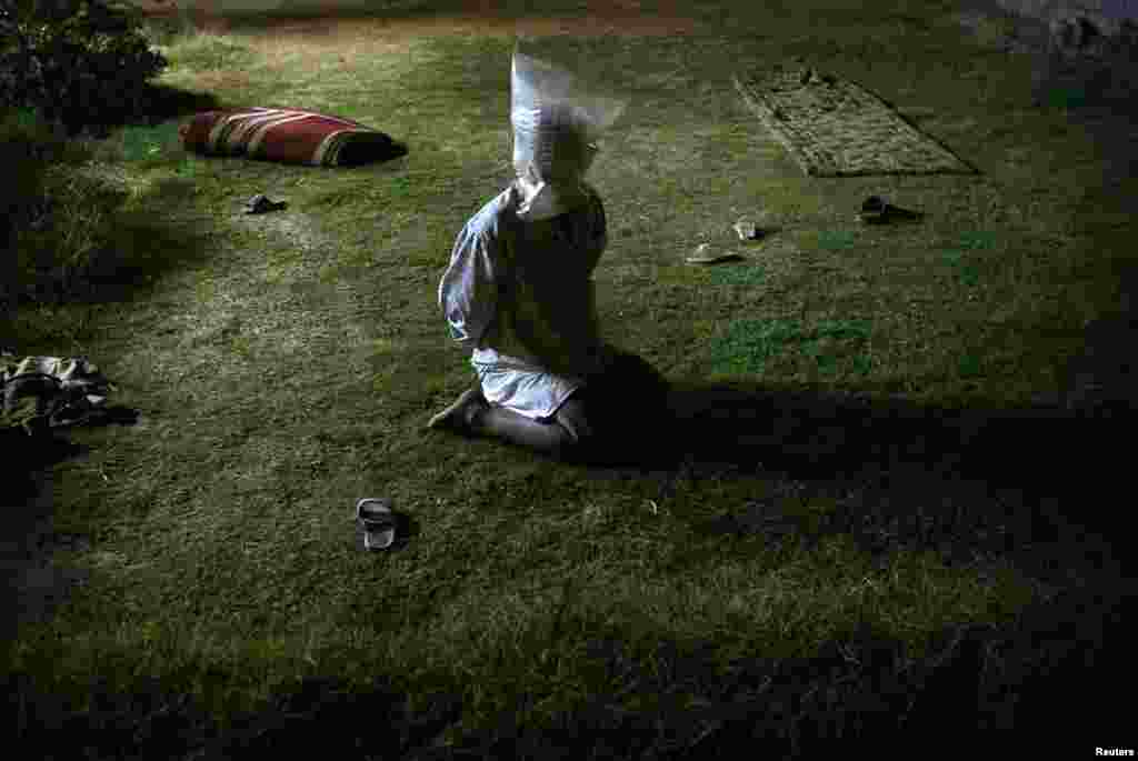 A detained Iraqi man with a plastic bag covering his head sits in garden of a house searched by U.S. soldiers during a night raid in Tikrit, Oct. 30, 2003.