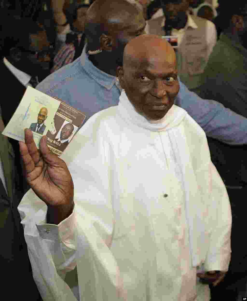 Le président Abdoulaye Wade présentant un bulletin de vote avant de voter au bureau de vote du quartier Point E, à Dakar (AP)